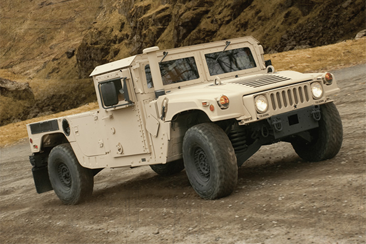 AM General M1152 Humvee drives uphill on off-road trail