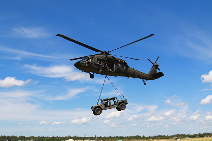 an AM General Humvee is airlifted by a Blackhawk Helicopter