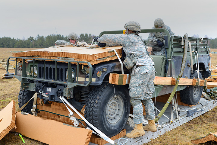 U.S. Army Paratroopers prepare an AM General Humvee that was airdropped by a C-130 Airplane during a training excercise