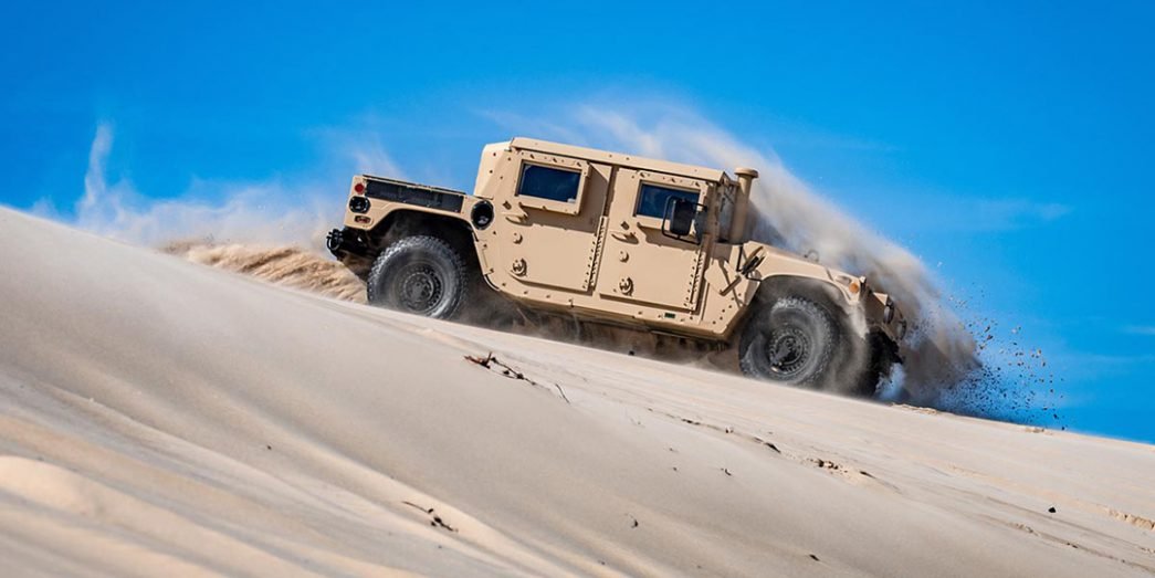 AM General Humvee drives down a sand dune