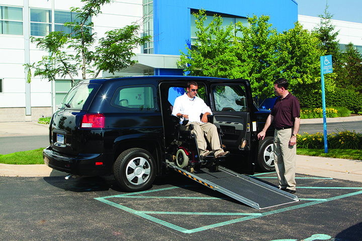 A disabled man uses the handicap ramp of an AM General MV-1