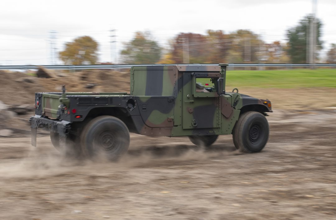 M1152 with Woodland Camo speeds by on an off-road course