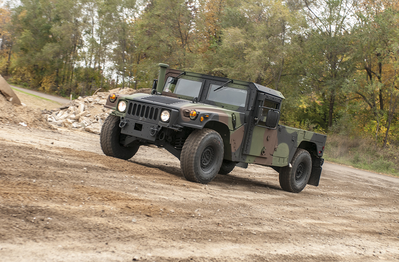 M1152 Humvee with Woodland Camo traveling uphill on a dirtroad