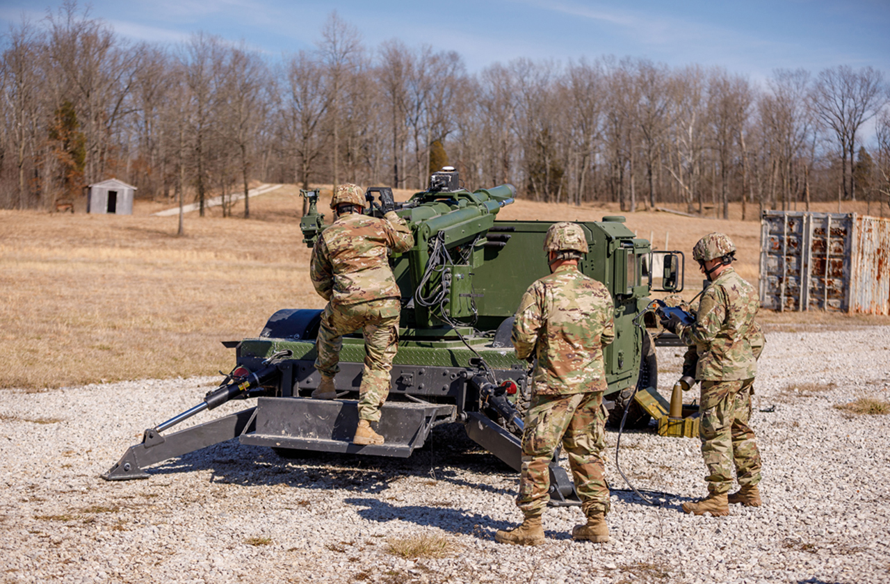 Three U.S. Soldiers aiming AM General's Mobile Howitzer Hawkeye artillery cannon
