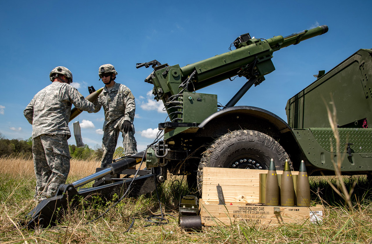 Two U.S. Soldiers operating AM General's Mobile Howitzer Hawkeye