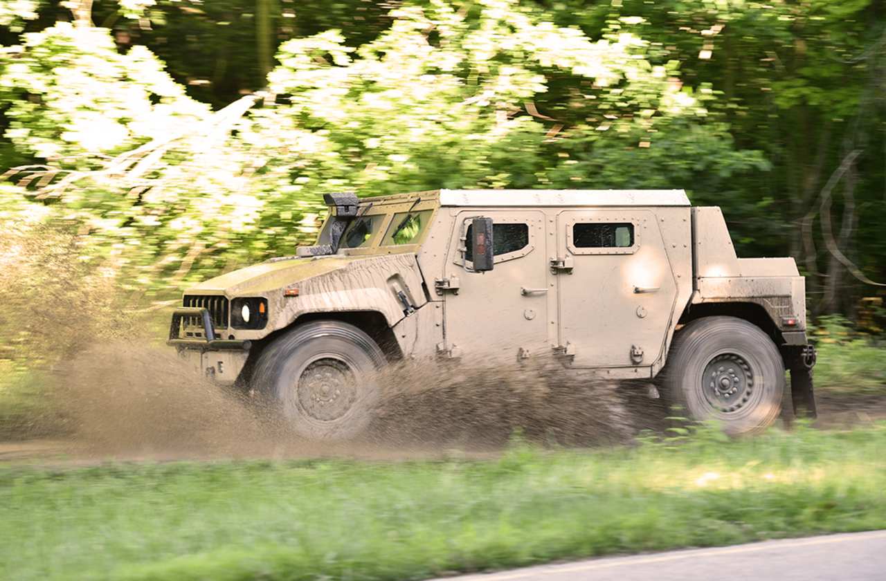 AM General Multi-Purpose Truck splashing through the mud on an off-road track