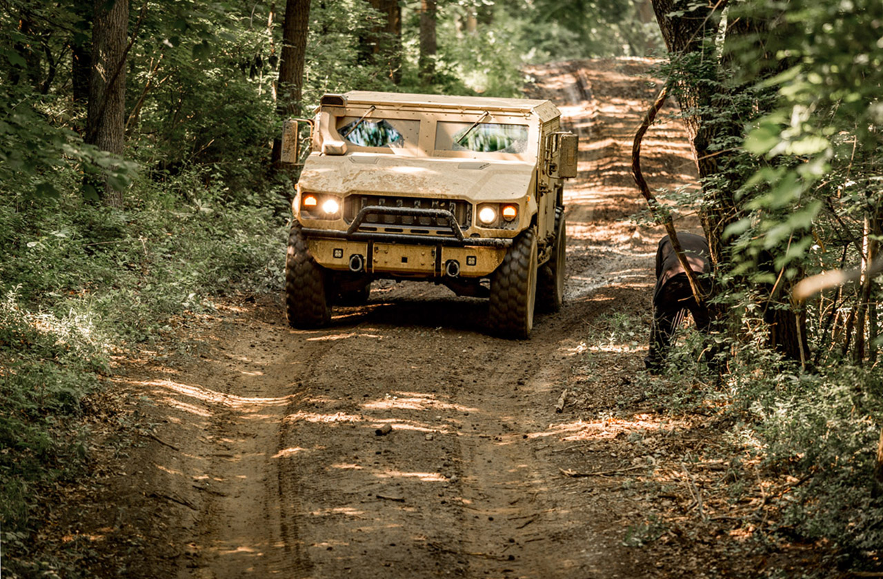 AM General Multi-Purpose Truck (MPT) driving on a dirt road through a forest